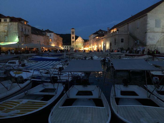 Sailboats moored in city at night