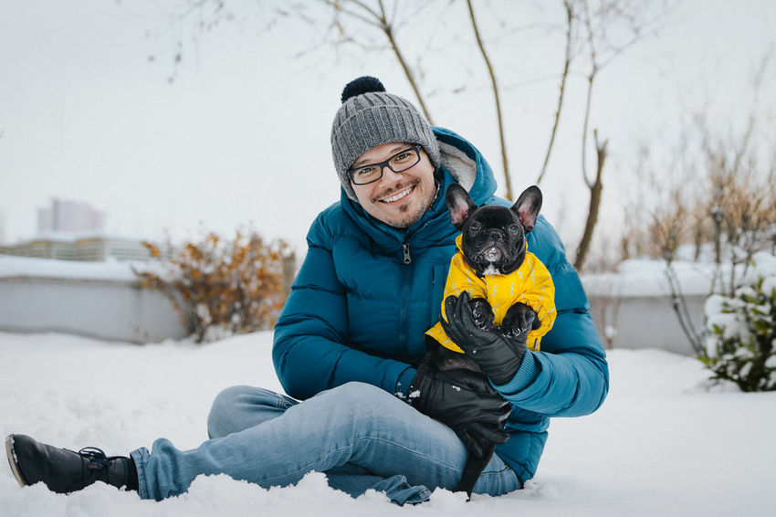 Winter Looking At Camera Pet Togetherness Bonding Puppy French Bulldog Frenchbulldog Frenchie Purebred Dog One Person One Man Only One Animal Pets Dog Domestic Animals Snow Covered Warm Clothing Snow Smiling Cold Temperature Happiness Portrait Full Length Winter Coat Knit Hat Glove Canine