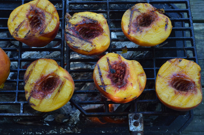 Peach halves grilling on top of a small tabletop Hibachi grill on picnic table outdoors Arrangement Close-up Dessert Desserts Full Frame Grill Grilled Peaches Grilling Healthy Eating Hibachi Grill Multi Colored No People Peach Peach Halves Peaches Sweet Food Variation