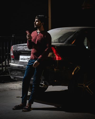 Full length of young man looking away while standing on car at night