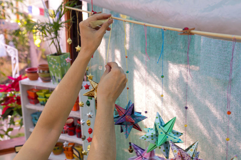 Craft fair, arm of woman choosing origami to buy