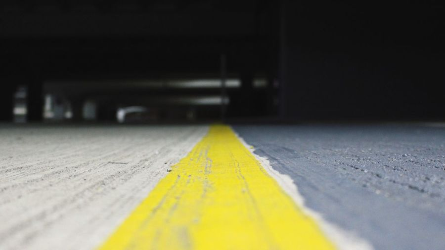 Follow the yellow line. The Way Forward Outdoors Close-up Surface Level Yellow No People Carpark Grey Upcloseandpersonal Horizontal Tarmac Floor