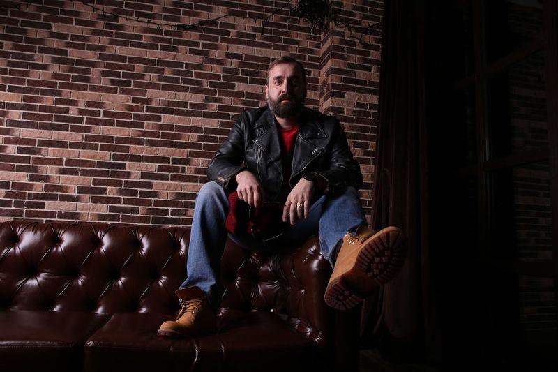 Full Length Of Fashionable Man Sitting On Sofa Against Brick Wall