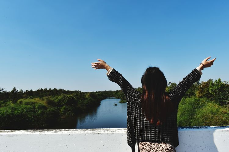 Rear view of woman with arms raised standing on bridge against sky