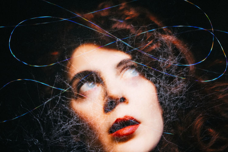 Digital composite image of woman looking through broken glass