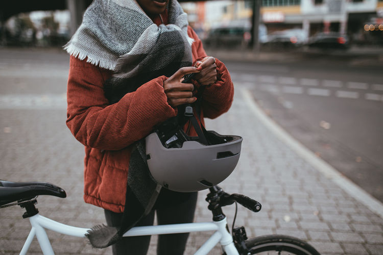 Midsection of woman with bicycle on footpath
