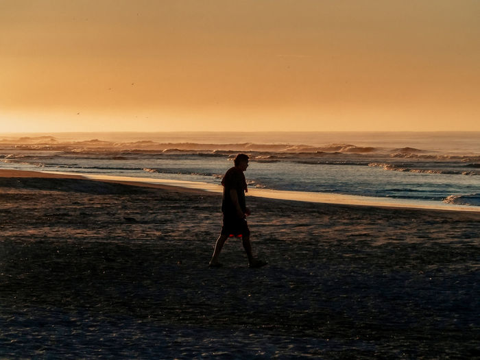Silhouette man walking at beach against clear sky during sunset