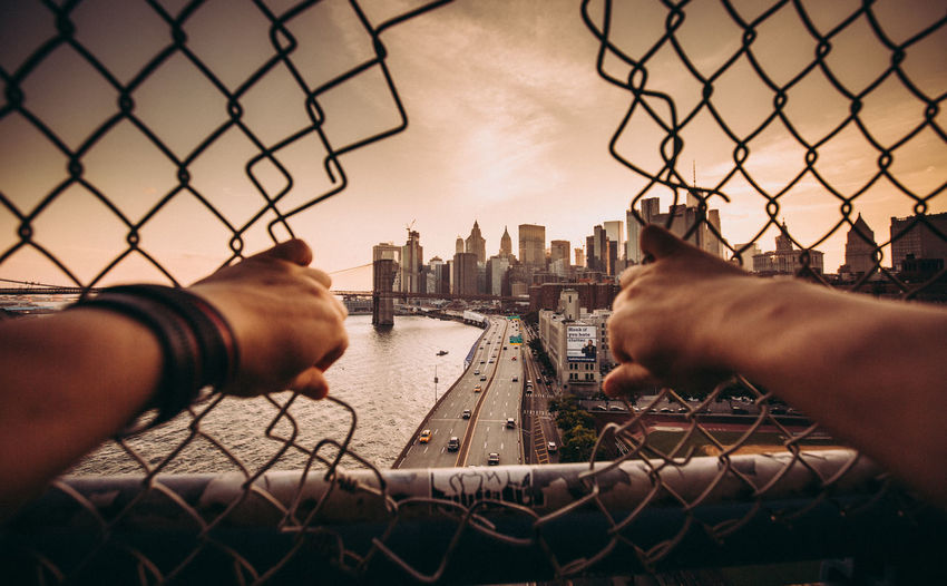 Cropped image of hands holding fence against sky in city