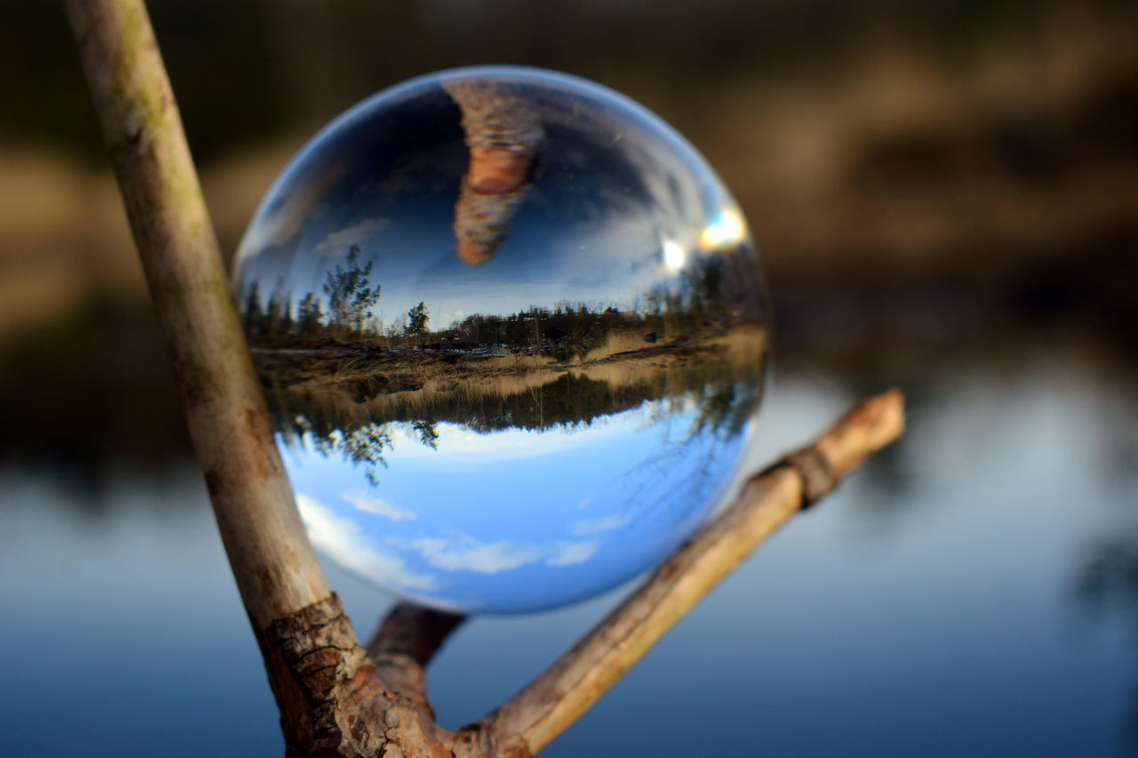 CLOSE-UP OF CRYSTAL BALL ON WATER SURFACE
