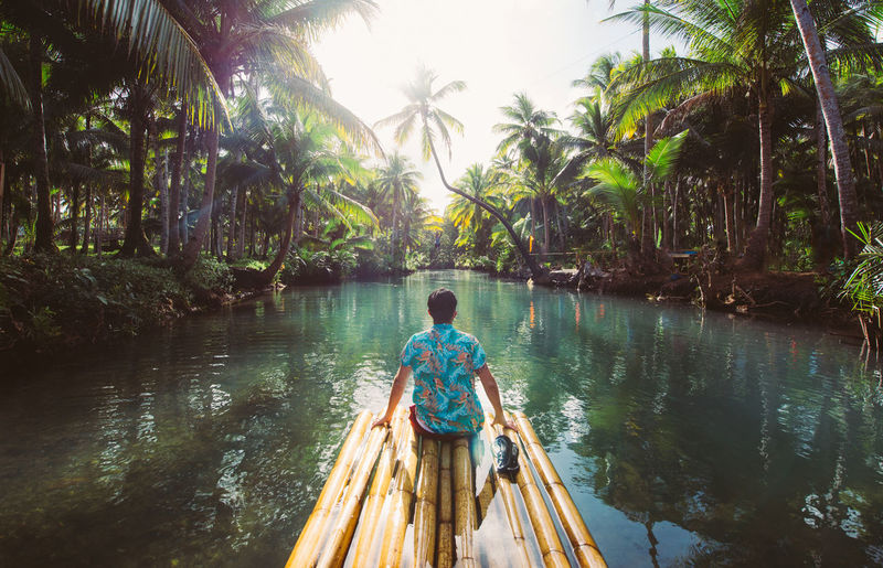 Rear view of man sitting on wooden raft in river