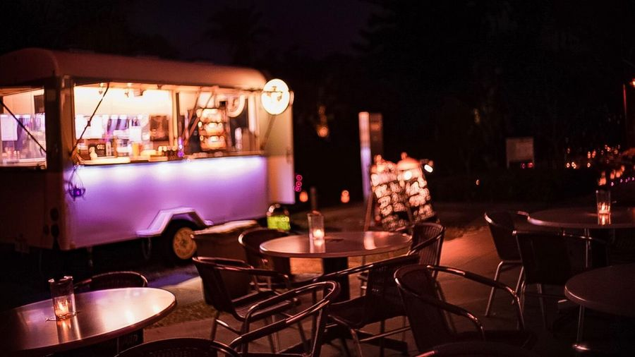 Empty chairs and tables at outdoor cafe in illuminated city at night