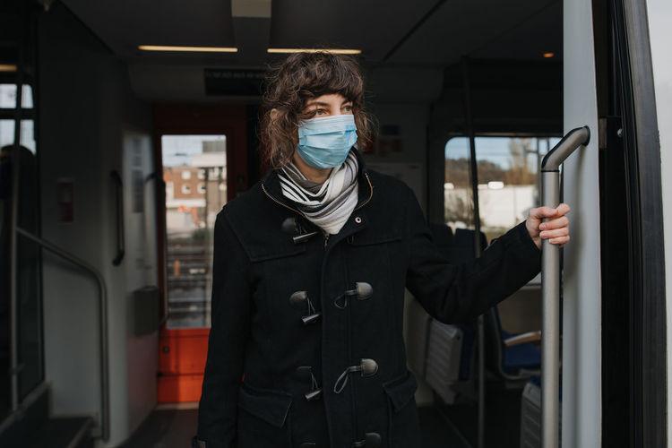 Woman wearing mask standing by train on railroad station platform