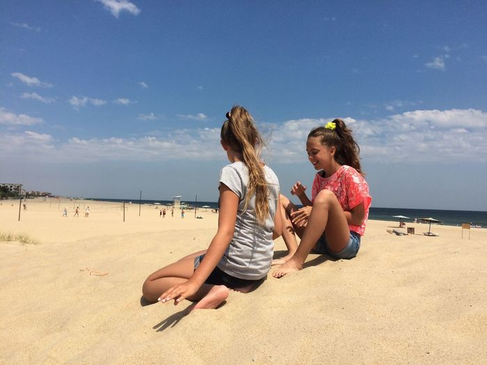 Teenage female friends relaxing at sandy beach against sky on sunny day