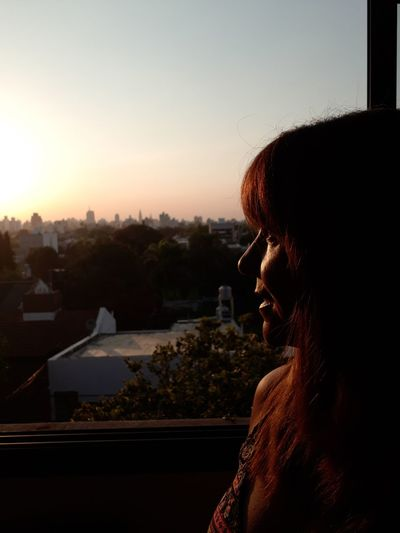 Close-up of woman looking at city through window during sunset