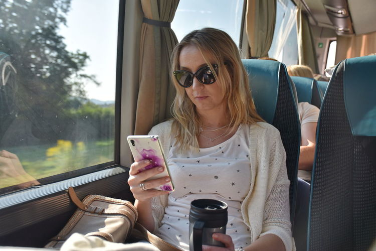 Woman using mobile phone while sitting in bus