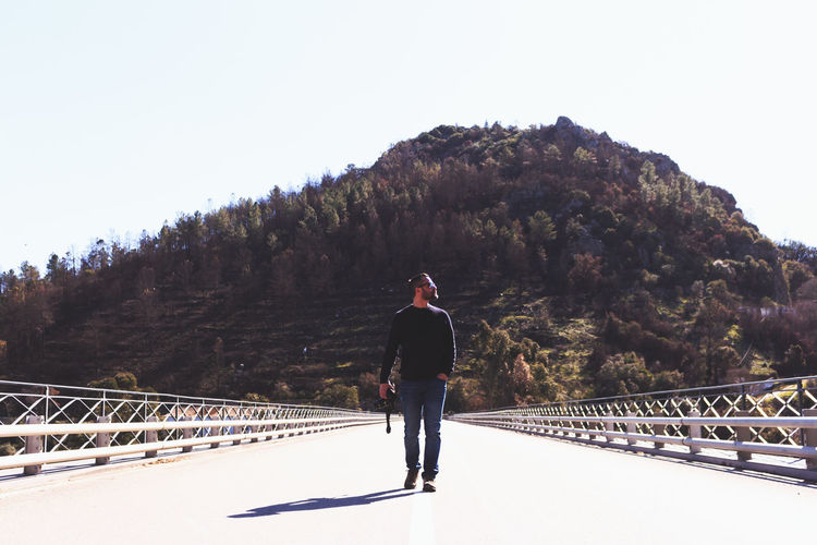 Full Length Of Man Walking On Bridge Against Mountain During Sunny Day