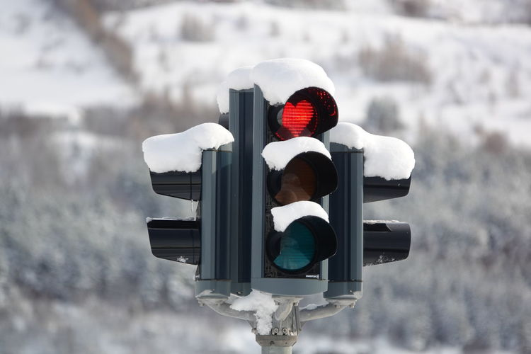 Road sign on snow covered street light
