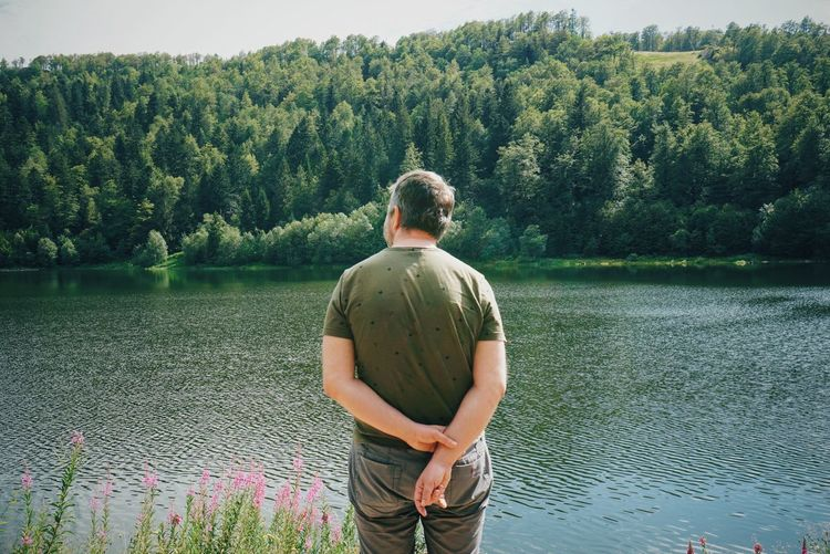 Rear view of man looking at lake against trees