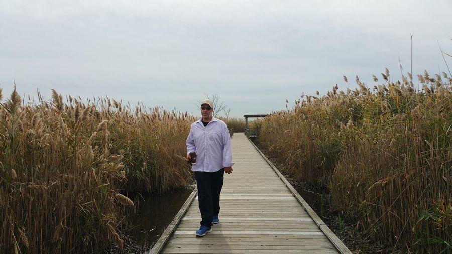 Mature man walking on boardwalk amidst grass against sky