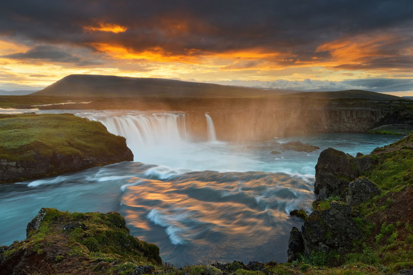 Scenic view of a waterfall in a wide sunset landscape, the colorful light reflected in the water, dark clouds above the scene - Location: Iceland, Goðafoss Godafoss Fall Godafoss Iceland Travel Beauty In Nature Cascade Cloud - Sky Colorful Colorful Sky Idyllic Long Exposure Motion Nature No People Orange Color Outdoors River Scenics Sky Sunset Tranquil Scene Tranquility Travel Destinations Water Water Motions Waterfall Wide Area Network