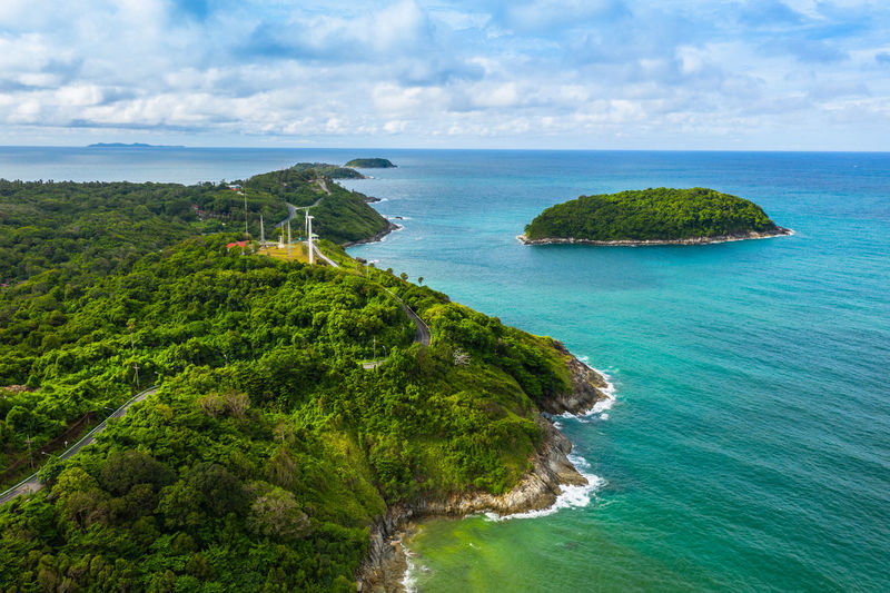 aerial view panorama Phromthep cape and wind tubine viewpoint. Phromthep cape is a famouse landmark and popular sunset viewpoint of Phuket Thailand. Sea Water Scenics - Nature Land Beauty In Nature Beach Sky Tranquil Scene Plant Coastline No People Tranquility Nature Day Horizon Over Water Cloud - Sky Horizon Tree Outdoors Turquoise Colored Nai Harn Beach  Phuket,Thailand Travel Photography