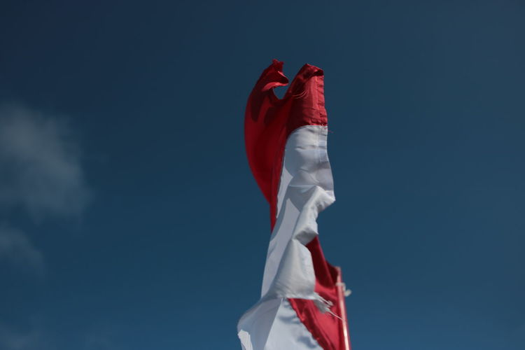 Low angle view of flag against blue sky