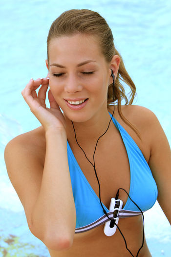 young blond woman listening to music with MP3 players at the pool Beautiful Happy Holiday Listening Music Music Summer Holidays Woman Beauty Bikini Blond Girl Happiness Happyness Leisure Leisure Activity Lifestyles Mp3 Player Pretty Relaxation Swimming Pool Vacation Water Wellbeing Young Adult Young Women