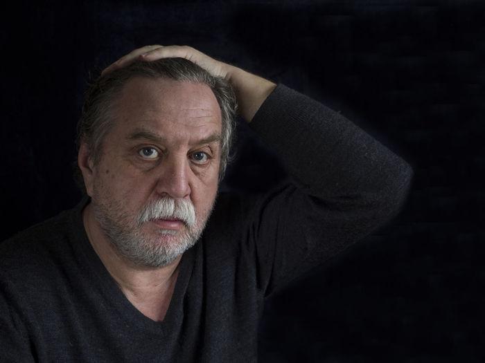 Close-Up Portrait Of Mature Man Against Black Background