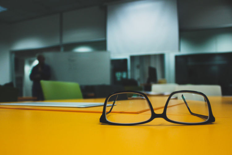 Close-up of eyeglasses on yellow office desk
