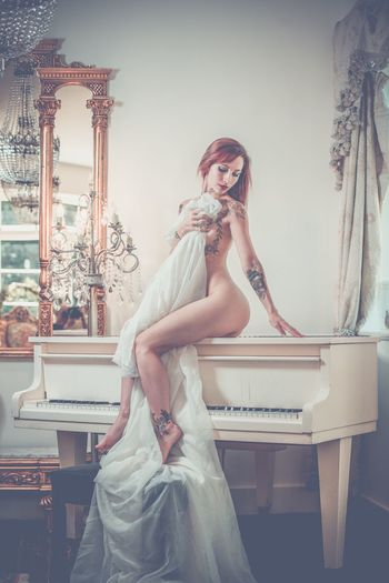 Side View Of Naked Woman Sitting On Piano At Home
