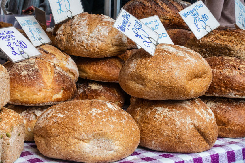 Loaves of bread on a stall in a farmers' market. Loaf Of Bread Baked Bread Choice Close Up Close-up Food For Sale Freshness Groceries Loaf Loaves Market No People Piled Up Price Tag Produce Retail Display Stacked Stall Store