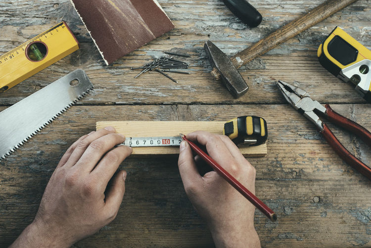 Cropped hands of carpenter measuring wood at table
