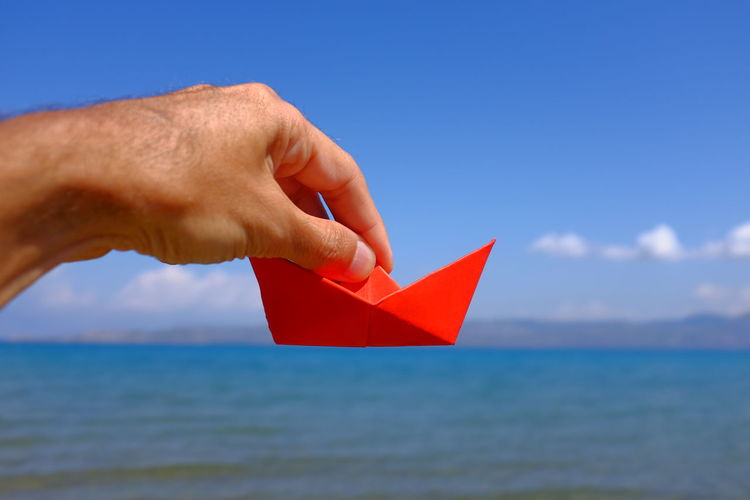 Cropped hand holding paper boat above sea
