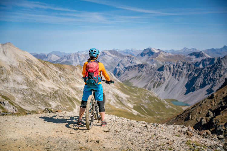 Full length of man riding bicycling on mountain against sky