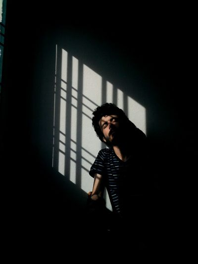 Young Man Sitting In Shadow Of Window