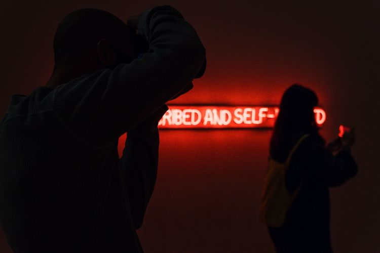 Rear view of man and woman standing against illuminated sign