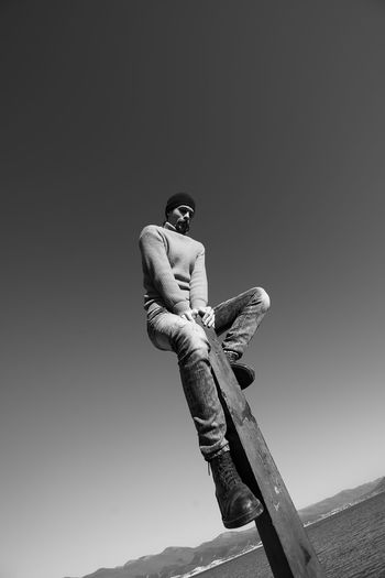 A young man does something interesting. It interacts with a wooden pile on the seashore. One person in the frame. Man on the background of a clear sky. He is warmly dressed in boots, jeans, a sweater and a hat. Casual wear. The guy wears a mustache and stubble. Hair out of the caps. Winter sunny day. Live black and white photo. Lifestyles Lifestyle Authentic Moments Authentic Candid Real People Blackandwhite Black And White Motion Sky Clear Sky One Person Low Angle View Human Hand Nature Day Men Hand Human Representation Full Length Outdoors Representation Casual Clothing Perspective People