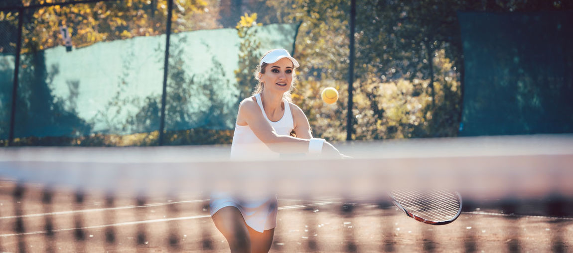 Woman Playing Tennis At Playing Field