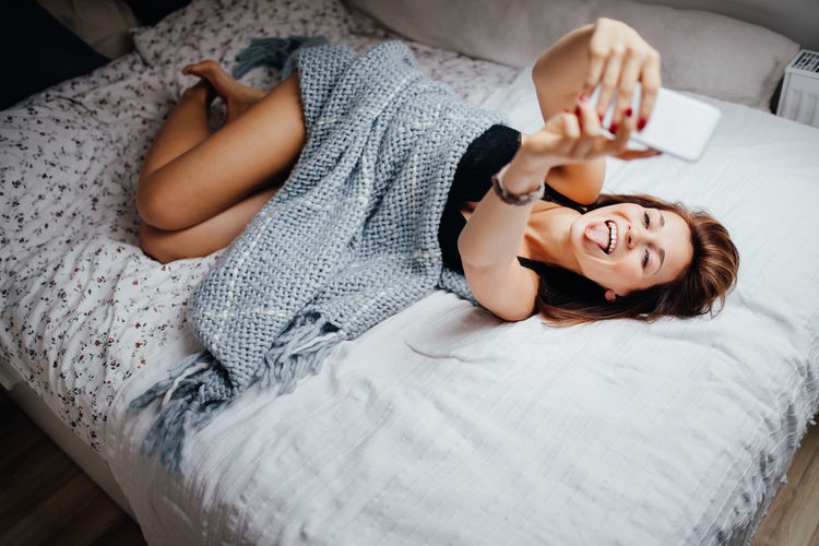 Woman taking selfie through mobile phone while lying on bed