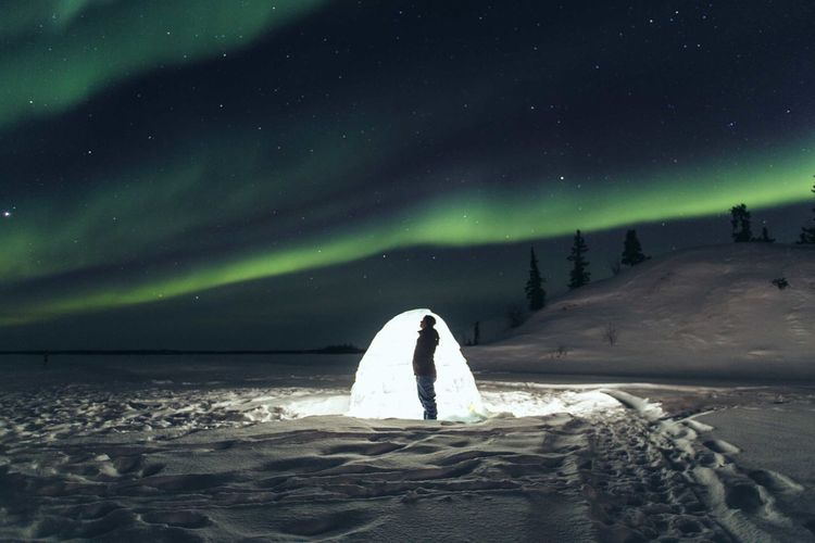 Man Standing By Illuminated Tent On Snow Covered Field At Night