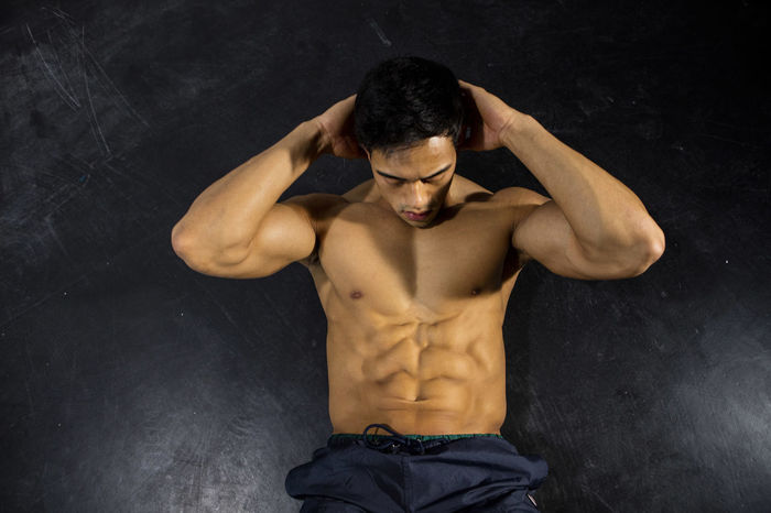 Male fitness model performing crunches. Overhead shot. Adult Asian  Athlete Body & Fitness Human Body Man Nam Vo Shirtless Sportsman Abs Crunches Fitness Model Grey Wall Hands On Head Handsome Hunk Male Muscle Muscular Build One Person Overhead Sit Ups Strong Studio Shot Torso
