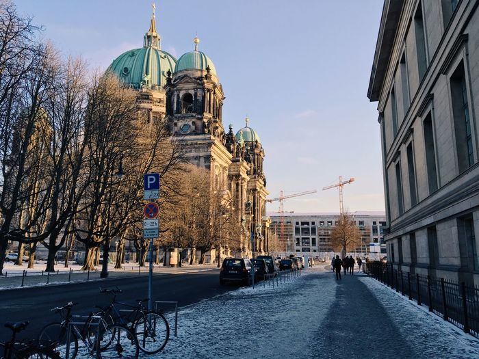 Snowy street by berlin cathedral against sky in city