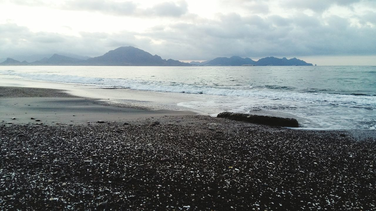 sea, water, beauty in nature, nature, scenics, beach, sky, tranquility, tranquil scene, shore, cloud - sky, outdoors, no people, horizon over water, sand, day, mountain, wave, pebble beach