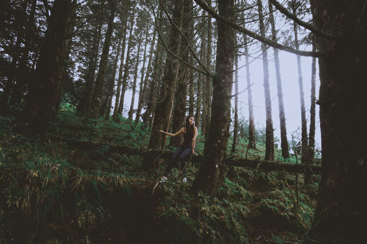 Young woman amidst trees in forest