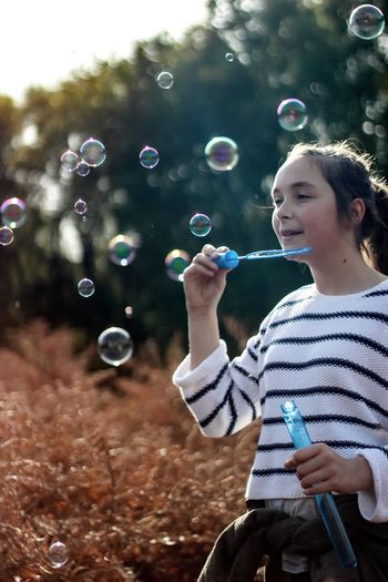 Bubbles Bubble Wand Bubble Soap Sud Leisure Activity Real People Childhood Waist Up Cheerful Carefree One Person Happiness Holding Fun Fragility Tree Smiling Motion Outdoors Day Nature Girl