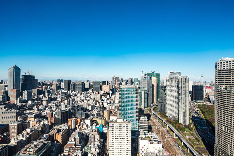 Aerial view of modern buildings against clear blue sky
