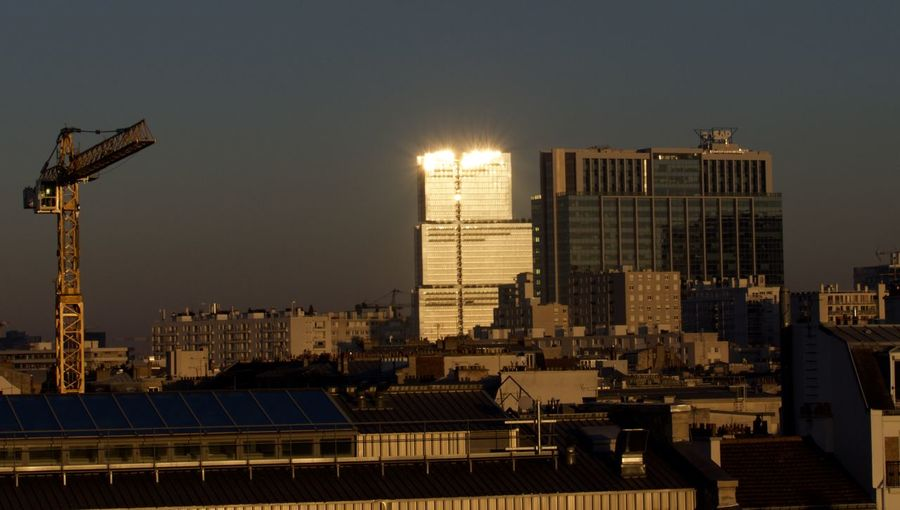 Illuminated buildings in city against clear sky
