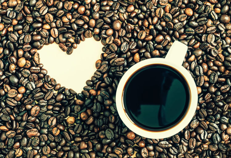 Close-Up Of Coffee Cup By Heart Shape Amidst Roasted Beans