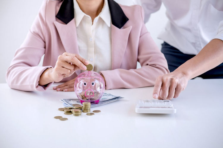 Growth Adult Business Coin Currency Finance Front View Hand Holding Human Hand Income Indoors  Inserting Investment Men People Piggy Bank Pink Color Profit Responsibility Retirement Savings Table Wealth Women