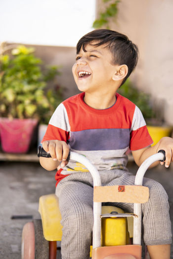 Boy sitting on toy car